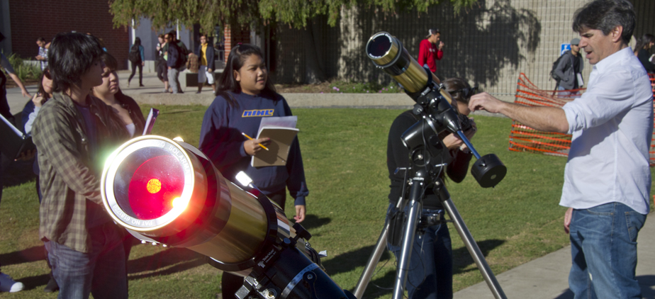 Astronomy students looking through telescopes