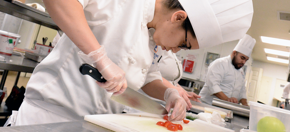 Culinary student chopping tomatoes