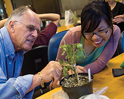 faculty and student examining a plant