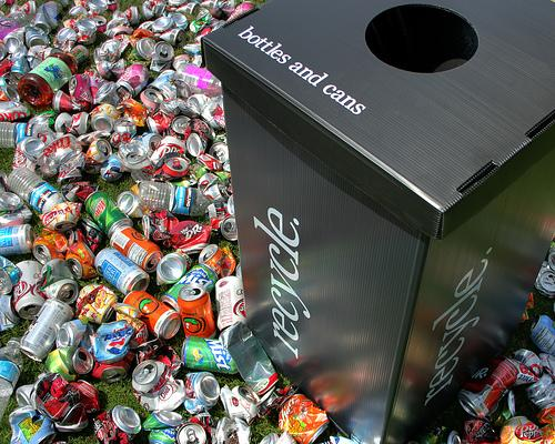aluminum cans littered around a recycling bin