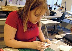 Female architect works on a design using paper and rulers
