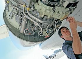 Maintenance worker works on engine of plane