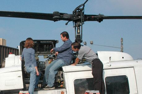 Group Of Maintenance Workers Work On Helicopter
