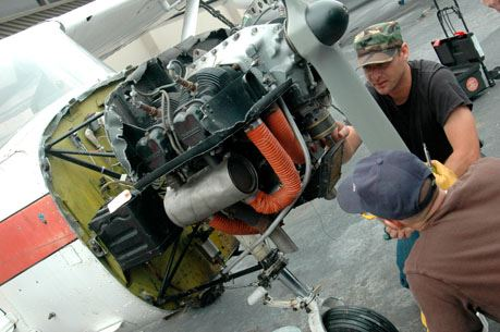 Two male maintenance workers inspect front rotor engine of plane