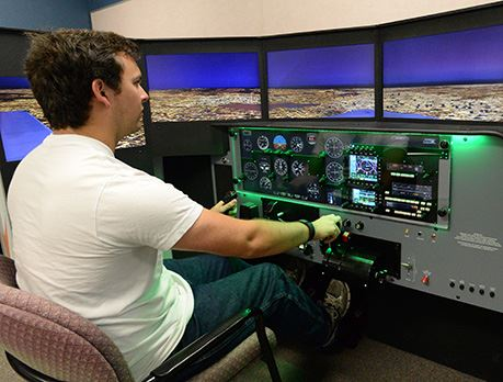 Man in white shirt practices flying plane on flight simulation technology