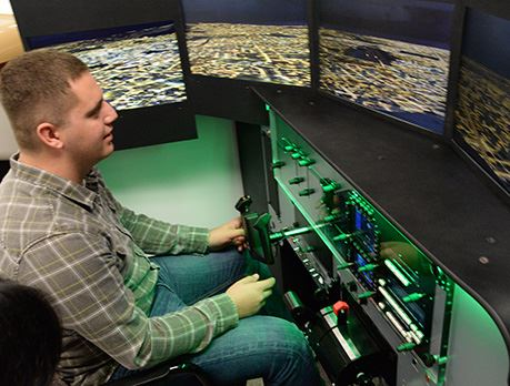 Main in grey plaid shirt practices flying plane on flight simulation technology