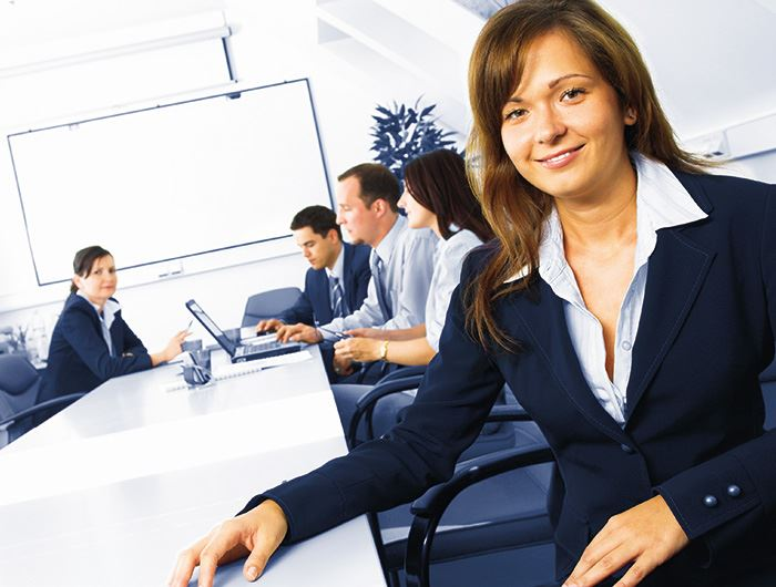 Woman in a business suit smiles at camera while her colleagues meet in the background