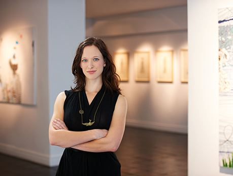 Woman in an art gallery poses for the camera with framed art in background