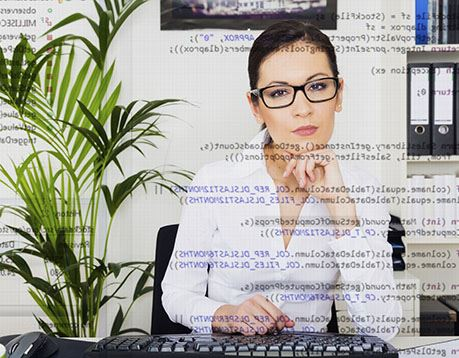Woman in white shirt and glasses works at computer and image includes coding as an overlay