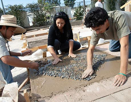 Three concrete workers create a design out of concrete and stone