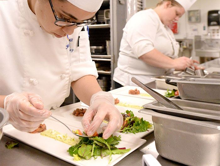 Culinary worker places garnishes on top of plates of salad
