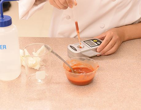 Close up view of a culinology assistant testing a red sauce with an instrument