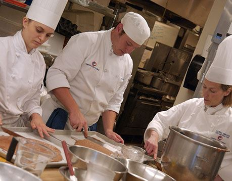 Three culinology professionals spread batter on a baking sheet