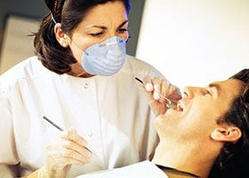 Female dental assistant uses tools to examine male patient's mouth