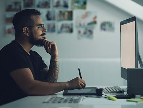 Male draws on a tablet while looking at a computer monitor