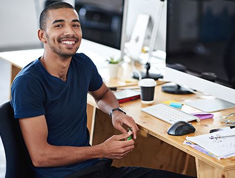 Male sitting at a computer work station smiles at camera