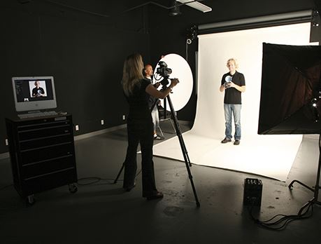 Woman takes a photograph of a man against a white backdrop in a photo studio