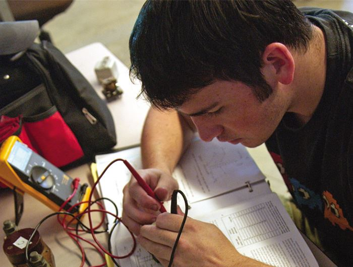 Electro-mechanical technician tests the electrical current of a part using a measuring instrument