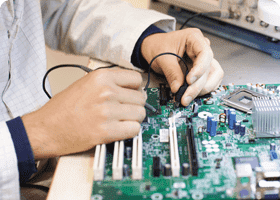 Electronics engineering technician works on a motherboard
