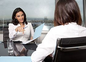 Woman in professional attire holds a folder and talks with another woman during a business meeting