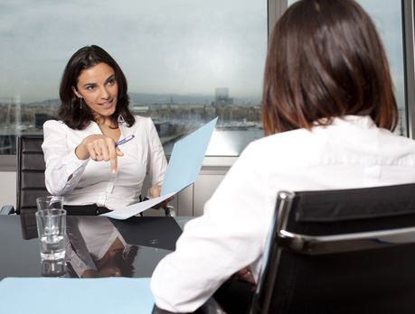Two business women holding folders sit across from each other at a desk