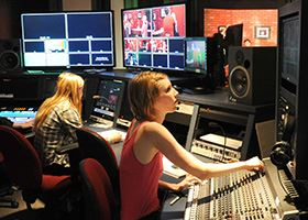 Female students works in a control room of a production studio