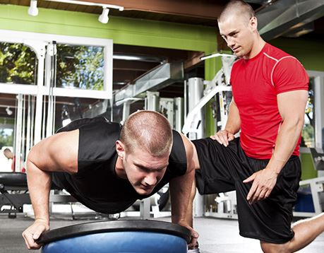 Male fitness specialist coaches male client during exercise session