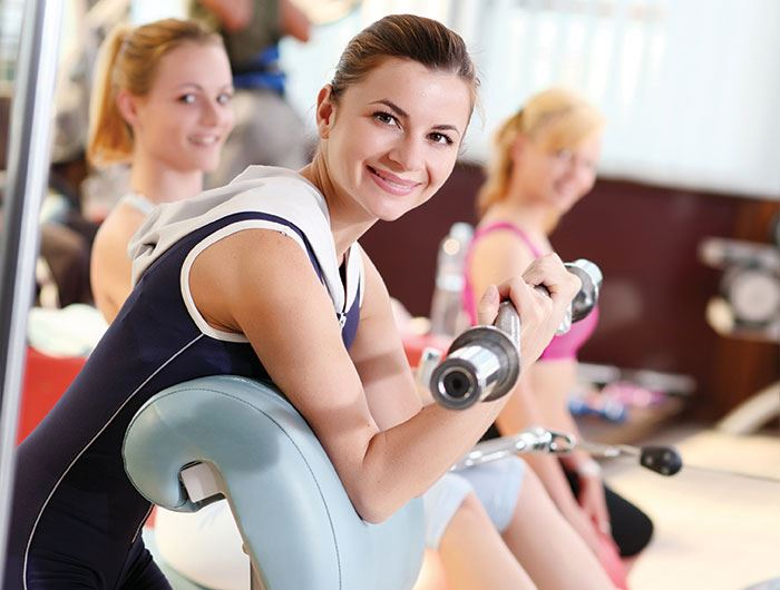 Female fitness client works out in gym