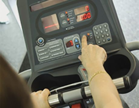 Female fitness client reviews exercise stats on treadmill