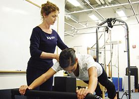 Female fitness specialist coaches female client in pilates