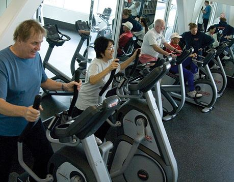 Group of people work out on stationary bikes in a gym