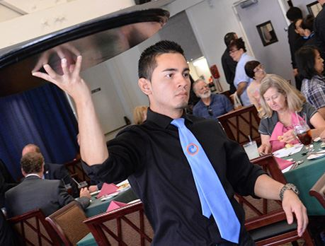 Waiter carries tray through busy dining room