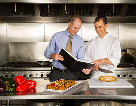 Food service manager consults with a cook as the two stand studying an open book while in a kitchen