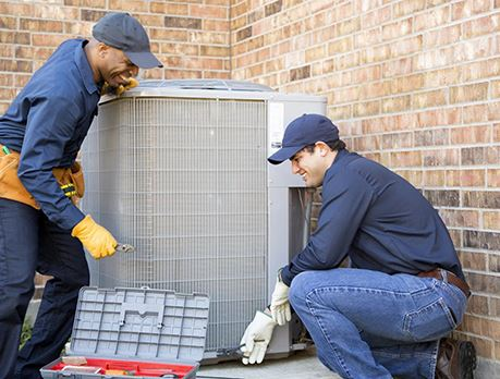 Two HVACR workers inspect an air-conditioning unit outside of a building