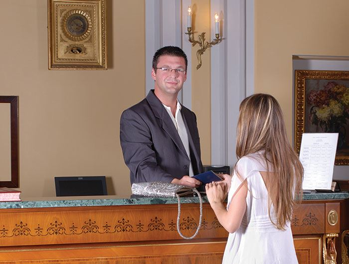 Hotel front desk manager checks in female guest