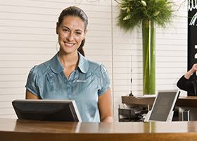 Female front desk manager in green shirt smiles