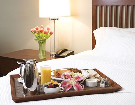 Tray of breakfast food on bed in hotel room