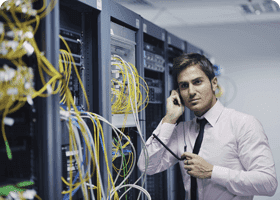 Male network administrator talks on phone next to computer servers