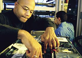 Male network technician works on computer motherboard