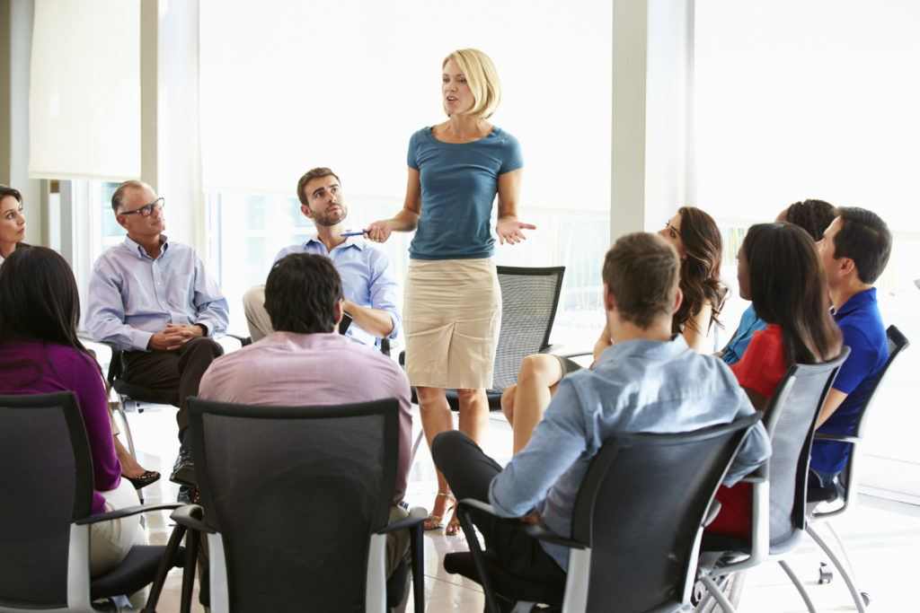 Business woman speaks standing in the middle of a circle of other business people sitting in chairs