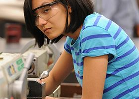 Female student in blue striped shirt and safety goggles leans over manufacturing machine