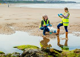 Two female marine scientists collect water samples from a shallow pool of water on the beach