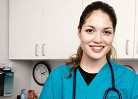 Medical assistant with stethoscope and vitals chart smiles at camera