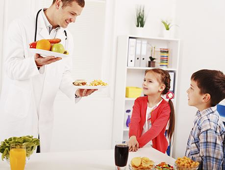 Nutritionist smiles and holds a plate of fruit and a plate of burgers in front of two young children