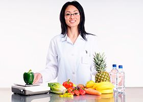 Nutritionist stands in front of a table with fruit, vegetables, water and a scale