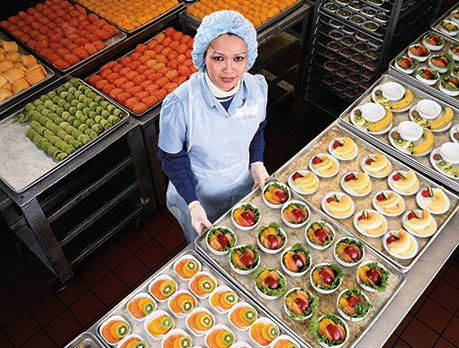 Nutritionist smiles in front of a table full of prepared fruit dishes