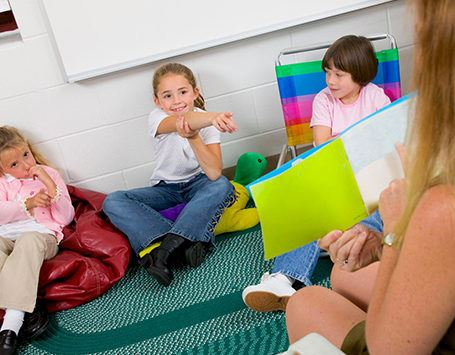 Teacher reads a book to three toddlers sitting on the ground in front of her
