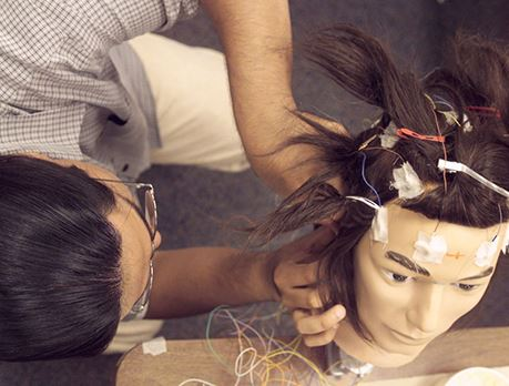 A student places electrodes on a training-manikin head