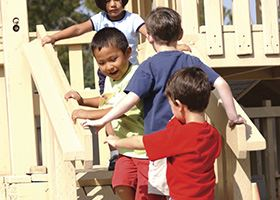 Four preschool students run up stairs together on a playground