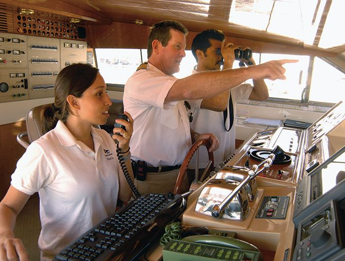 Three professional mariners navigate a ship while one looks through binoculars